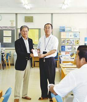 石塚会長(左)から澤尻校長に渡された