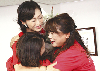選挙事務所で関係者と抱き合って喜ぶ三原氏(中央)