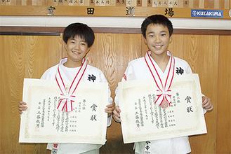 メダルと表彰状を手にする飛田さん(左)と小寺君