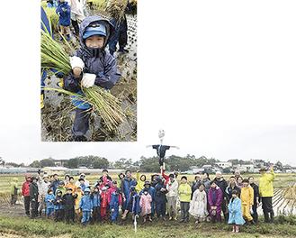 自ら刈り取った稲を手に笑顔。この日は悪天候の中、家族も含めて40人が参加した