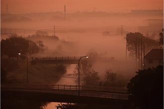 天気予報で「明日はモヤが出る」という言葉を聞き逃さず、当日の朝に自宅のベランダから一眼レフを構えて撮影した藤平さんの「朝霧」
