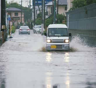 大曲橋近くの住宅地で冠水地点を進む車