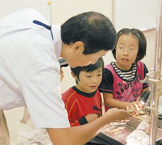 大平助教授(左)が大学の実験器材での観察を指導