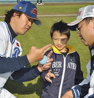 鈴木尚典氏(左)が親子にボールの握り方を直伝