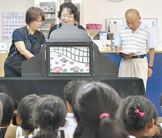 子どもたちの前で紙芝居を上演する観光サポーター