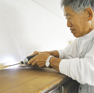 食器棚と壁を木材で固定する菅家さん