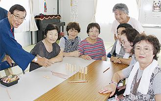 絵付けした童像を囲む山田会長(左)と石巻市民