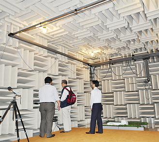 騒音対策の実験を行う「無響室」。天井、壁、床の下にいたるまで吸音材が内装されている。右下は実験に使用した車と植え込みの模型