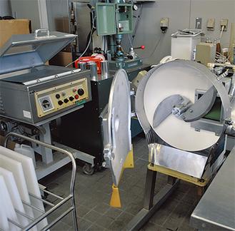 左から真空包装機、缶詰巻締機、野菜などを大量に速く切る大型カッター。他にも多種多様な機械が揃う