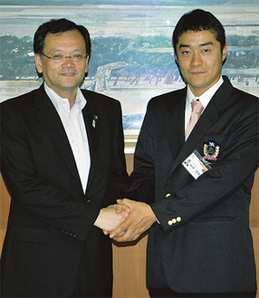 落合市長と握手を交わす樹神さん(右)