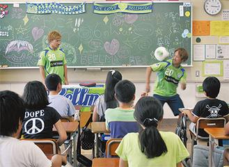 児童の声に応え、リフティングを披露する猪狩選手(右)