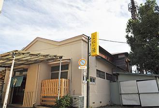 黄色い看板と店舗裏手の煙突が目印。建物は戦後に再建した