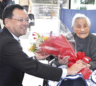 玄関ホールで落合市長から花束を受け取る石黒さん