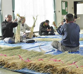 足と手を使い藁を編んでしめ縄を作っていく