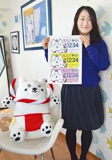 磐田市から贈られた副賞の「しっぺい」ぬいぐるみと並びデザインを持つ木村さん