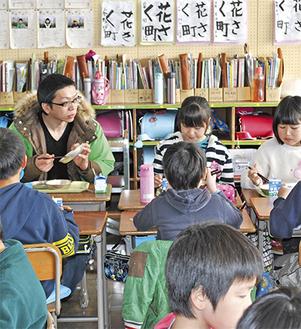 児童らと会話しながら給食を楽しむ井澤さん(左)