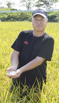 はるみ米を手に畑に立つ小川さん