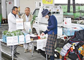 農産物の説明をしながら接客する出店者