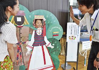 民族衣装が描かれた顔出しパネルを楽しむ親子(右は市職員)