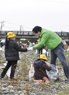 会員(右)とゴミを拾い集めた児童ら