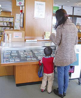 カウンター前に展示された怪獣ブロマイドを見学する親子