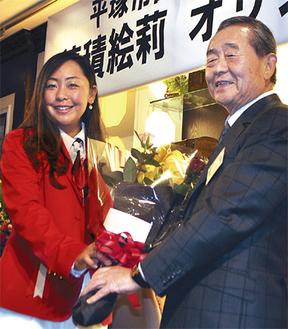 会場となったサンライフの竹内惠司会長から花束を受け取る穂積選手