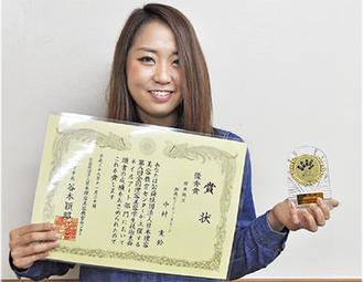賞状と盾を持ち笑顔の中村さん