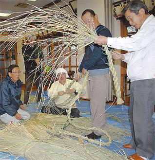 わらを素手で編む様子=八坂神社で15日
