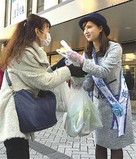 リンゴの入った袋を手渡す小嶋栞さん(右)