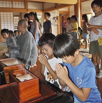 焼香体験で手を合わせる児童
