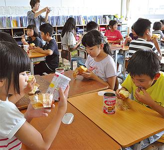 缶詰パンを試食する児童ら