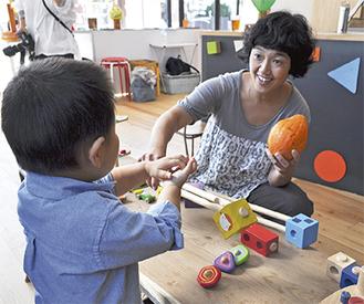 スタジオを利用する子供と遊ぶ石井さん