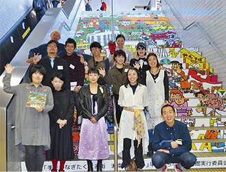 平塚の名所を絵画にした階段ラッピング前で記念撮影する参加アーティストたち