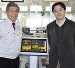 デジタルサイネージを囲む菊池代表(左)と浩さん