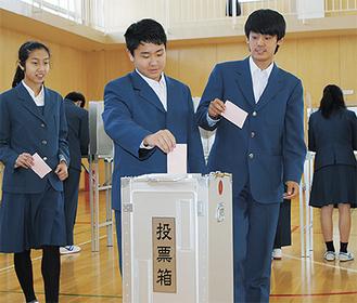 候補者名を記入して一票を投じる生徒ら