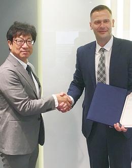 笑顔で握手を交わすミンドウガス・ビリウス会長(右)と木川大成担当部長