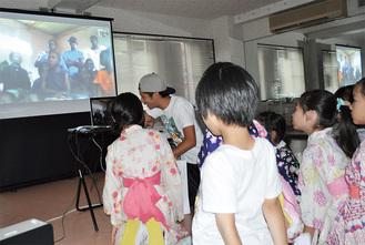 ザンビアと中継をつなぎ、英語で挨拶する子供たち