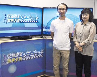 モニターとキャビネットの前に立つソフトを開発した三田村さん(右)と設計した佐野さん