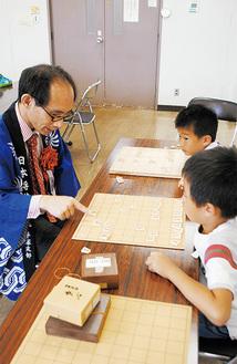 上野五段と対局する児童ら