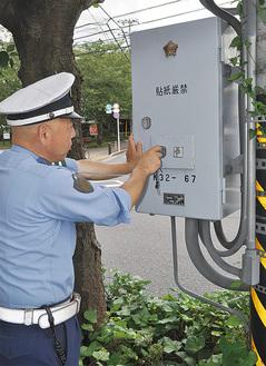 制御機を説明する署員(県合同庁舎前交差点で30日)