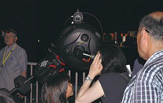 新型望遠鏡をのぞく来館者