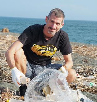 海岸でゴミを拾うタジさん