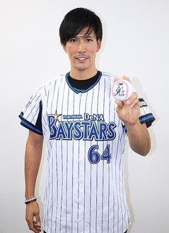 自身のサインボールを手に笑顔の古村さん
