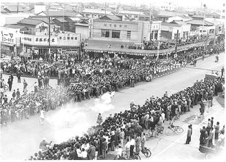 平塚(宮の前・明石町付近)を走る1964年東京五輪の聖火ランナー(市博物館提供)