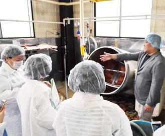 小豆に甘味を加える大型の鍋を見学する参加者