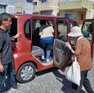 利用者を車に案内する送迎担当者(左)