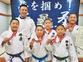 大会に出場したメンバーと金井監督(左上)