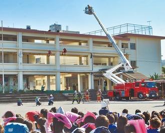 はしご車「シグマ」を使った救助訓練。救助隊がロープ一本で屋上から緊急脱出した。