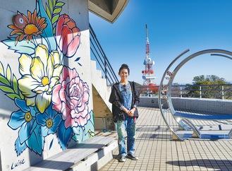 ルイーゼさんと作品。ainowaの横に壁画は描かれている。