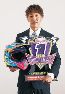 優勝盾とヘルメットを持つ佐々木さん